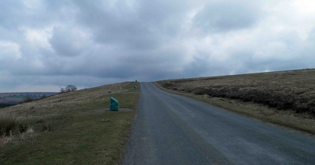 Salt grit bins line the steep moorland road