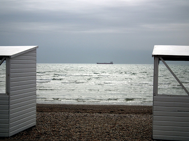 A ship glimpsed between the beach huts