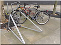TQ3282 : Cycle racks with locks left by commuters by David Hawgood