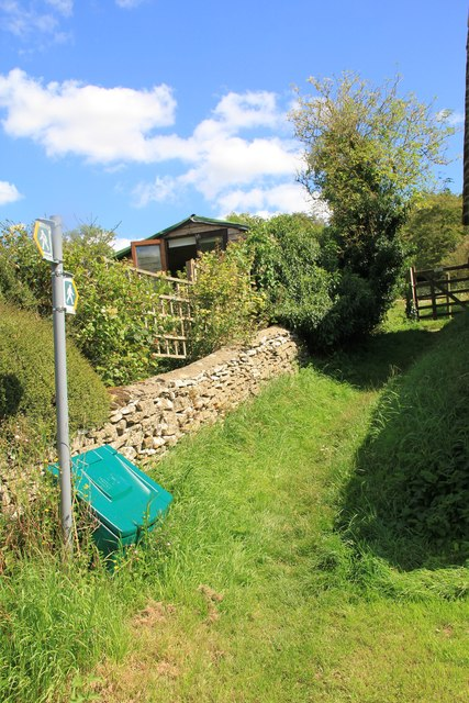Path climbs away from lane in Chedworth