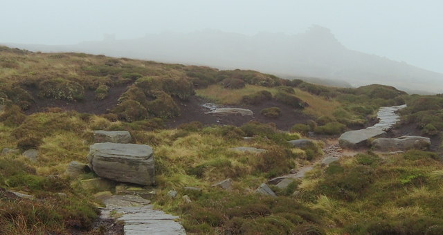 Moorland path and rocky outcrops in the mist