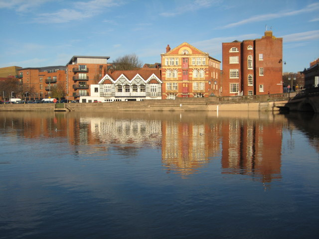 Buildings reflected in a flooded River Severn