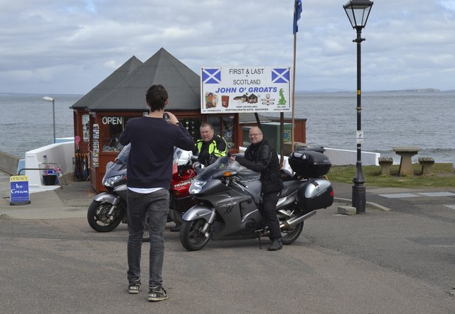 Bikers pose at the First and Last Sign at John O'Groats, Wick, Caithness
