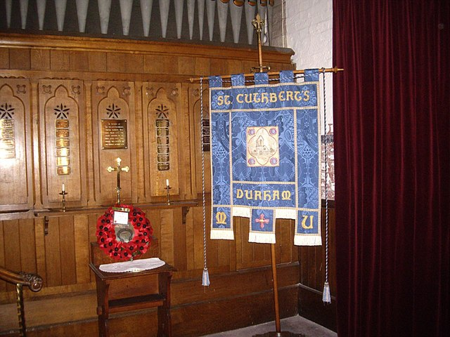 Wood-panelled organ screen bearing War Memorial dedications on small brass plaques