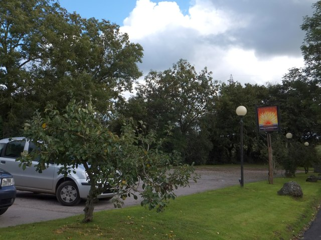 Car park and sign of the Rising Sun inn