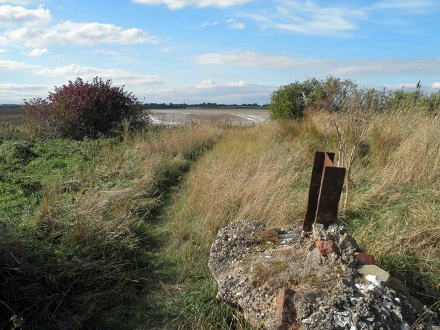 Old foundation and steel post open onto farmland