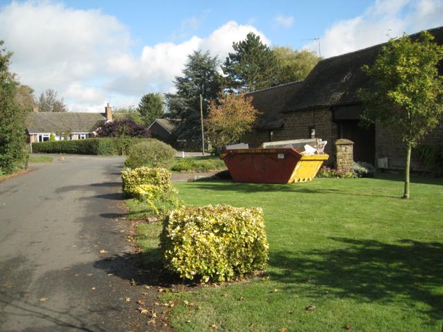 Roadside shrubs and skip, Elmers Farm, Priors Hardwick