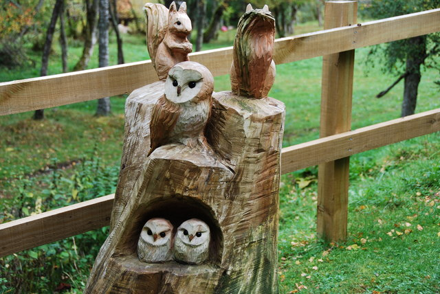 A family of Owls and squirrels all carved out of a tree stump