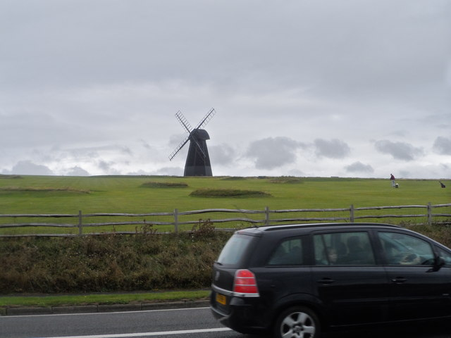 A car on the A259 passes in front of Rottingdean Windmill