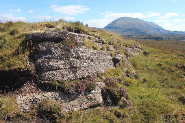 An outcrop, possibly Torridonian sandstone, stands out against the encroaching peat bog