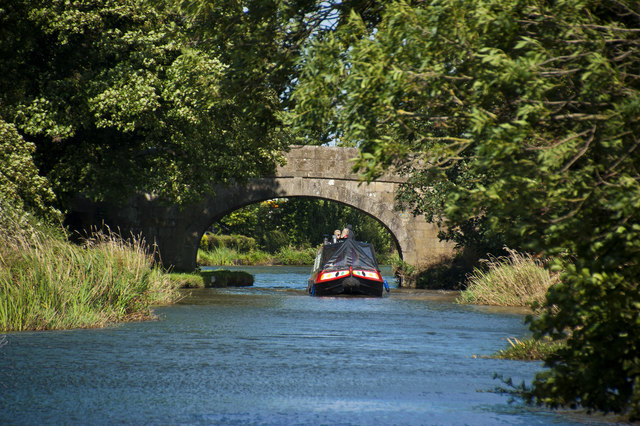 A canal boat navigates Bridge 48 on the Lancaster Canal