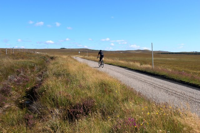 A happy cyclist pedals towards Lairg
