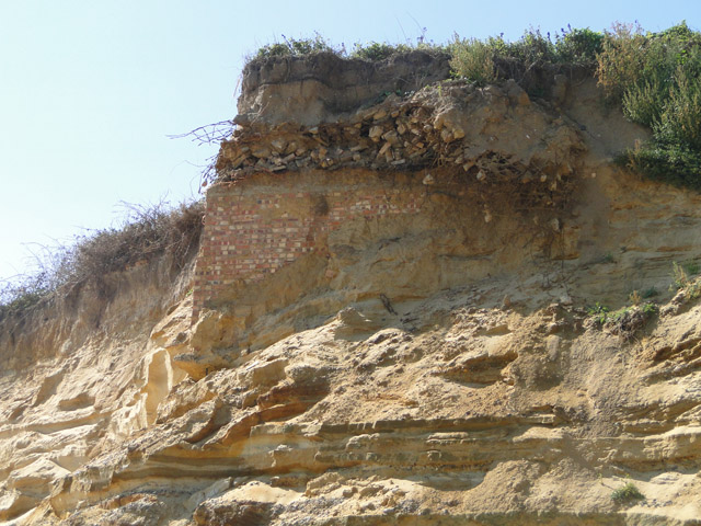 Subterranean building revealed in cliff-face, from the beach
