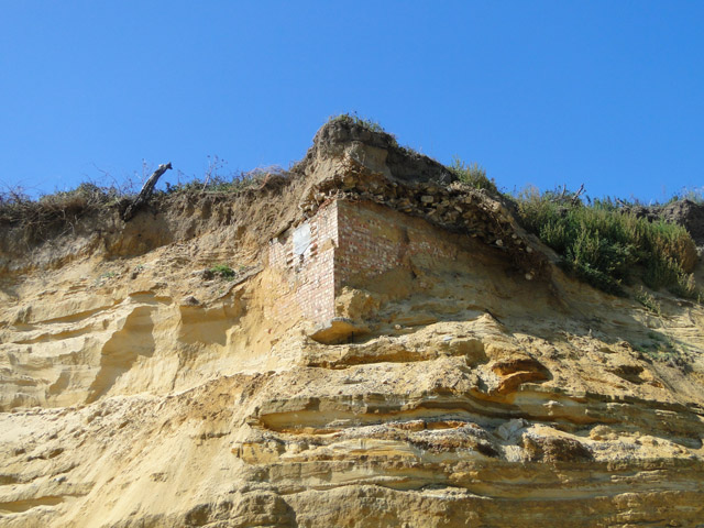 Subterranean building revealed in cliffface, from the beach