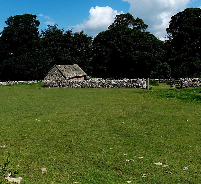 Farm building and a Cotswold stone wall in Miserden