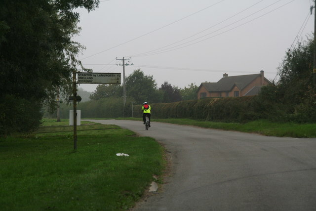 Signpost and cyclist on the Langworth Road into Scothern