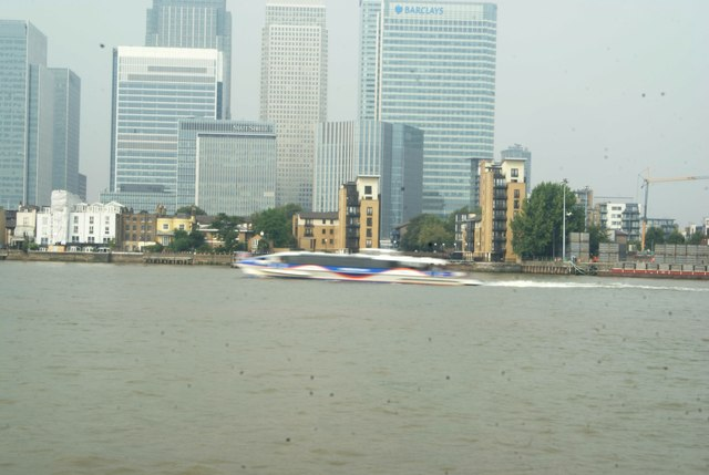 View of a Thames Clipper speeding past Canary Wharf