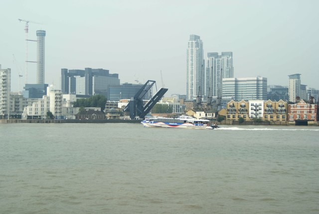 View of a Thames Clipper passing the opening West India Dock bridge