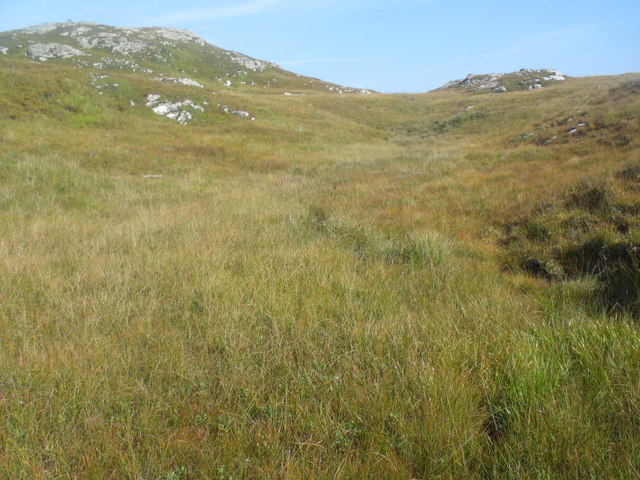 Stream hidden in grass before burying itself in peat below Cnoc Breac near Lochinver