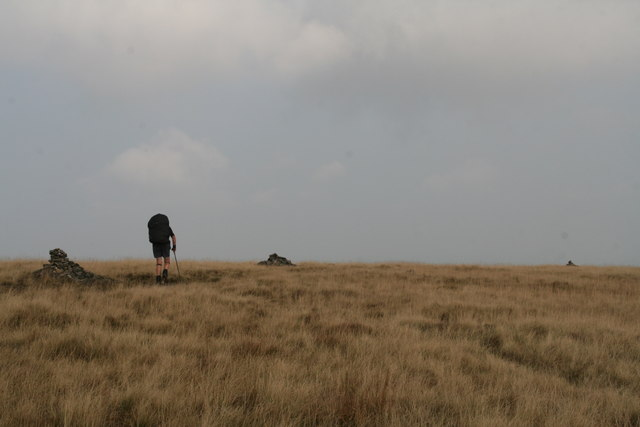 Three cairns and a hiker on the Pennine Way north of the Black Hill trig point