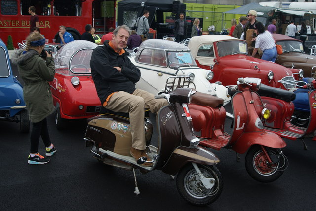 View of one of the Lambrettas with its owner sitting on it