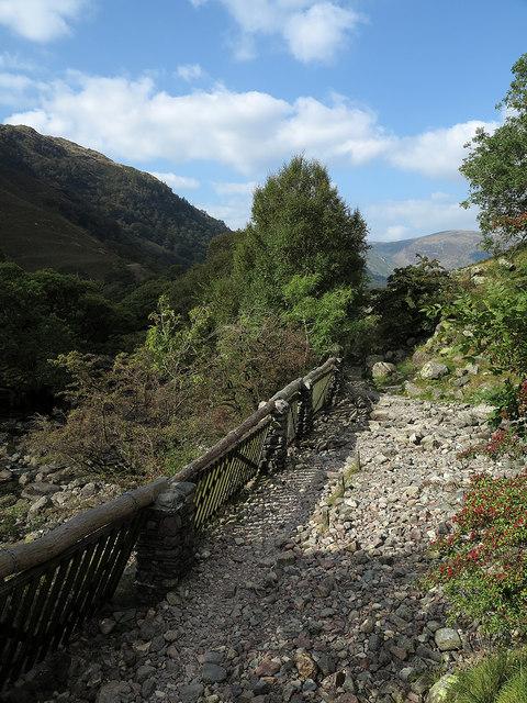 Stream gates in wall alongside path