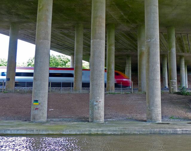 Virgin Pendolino train passing under the M6 motorway