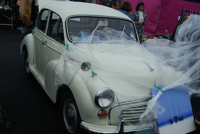 View of a Morris Minor acting as a support for a rain cover for a clothes stall