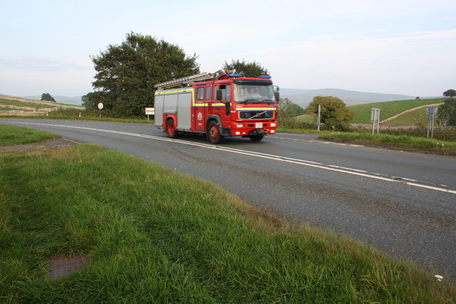 Fire engine hurries past the A683 junction from the A685