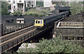A class 115 diesel multiple unit crosses the Euston mainline on the ex-Great Central Railway tracks into Marylebone.   This shot was taken from derelict land beside Alexandra Road before new housing was constructed on the corner.   The house on the top right of the photo has been reconstructed and the concrete hut on the bridge next to the train is now largely obscured by shrubs.