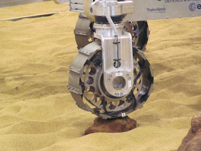 The Mars Rover Test Facility rolls over a small stone