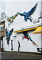 Macaw mural by Louis Masai on the Tilloch Street side of Euro Caf�, Caledonian Road.  The figures beside the doorway are the work of Pegasus.   Information from London Calling Blog.