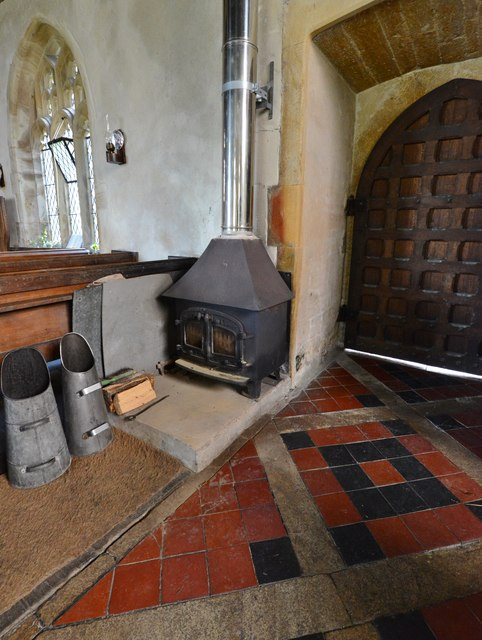 Melbury Bubb, St. Mary's Church: Heating is by means of this coal fire and wall mounted oil lamps