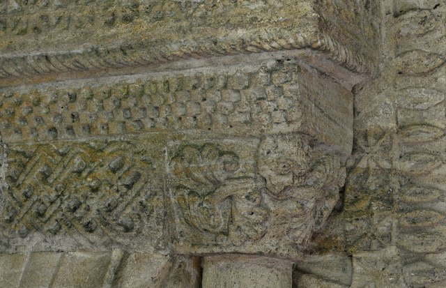 Quenington, St. Swithuns Church: The Norman north doorway, green man capital 2