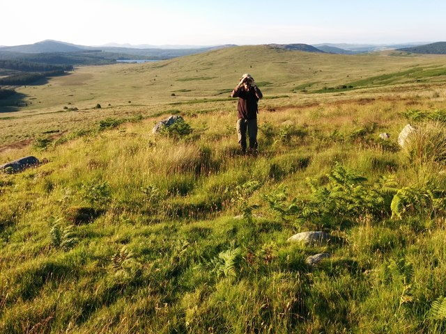 Hut circle? with man looking for giant buzzard. Loch Skerrow in distance