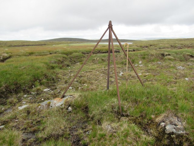 Wull at rest on straining post in view of Lochan Iain above upper Speyside