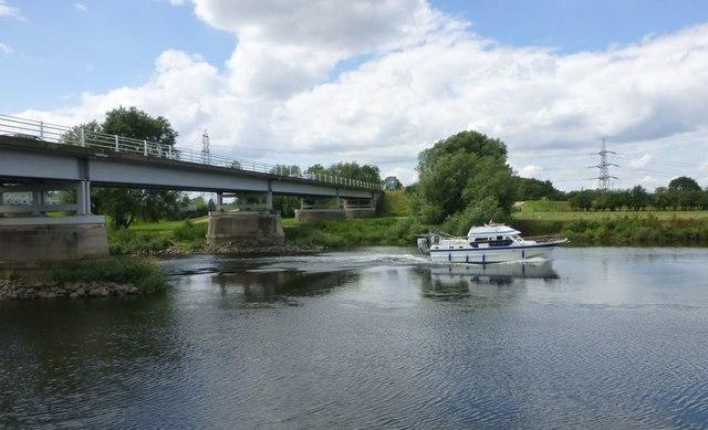 Cruising boat passes under Dunham Toll Bridge