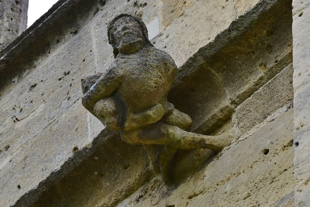Bishops Cleeve, St. Michael and All Angels Church: Sculpture of mason catching a boy climbing on the roof