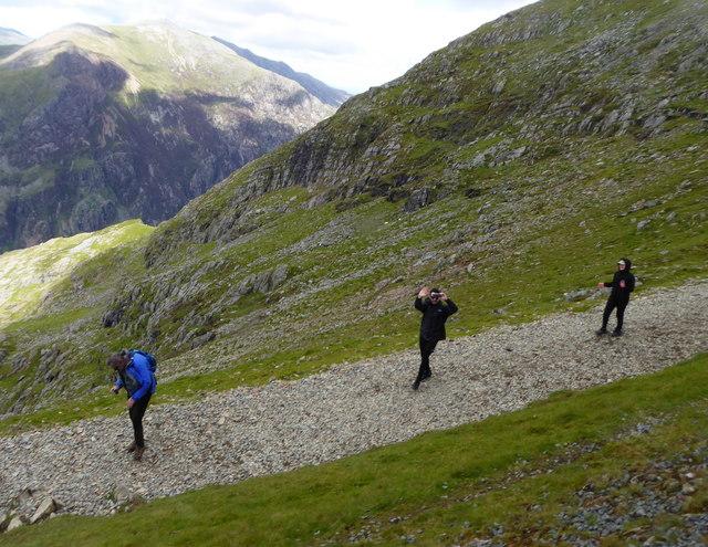 Walkers descending the Llanberis Path alongside the Snowdon Mountain Railway