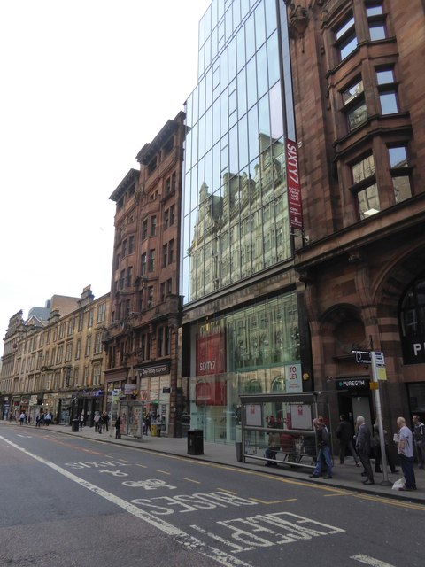 The glass of Sixty7 reflecting older buildings