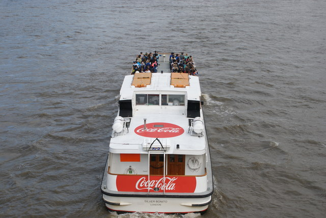 View of the Coca Cola London Eye River Cruise boat (Silver Bonito) passing under Westminster Bridge
