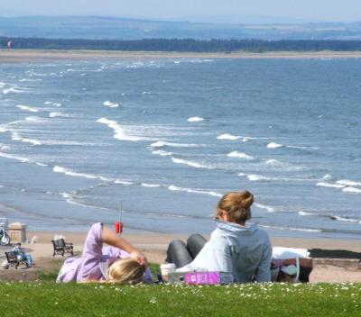 Students enjoying the sun at St Andrews bay