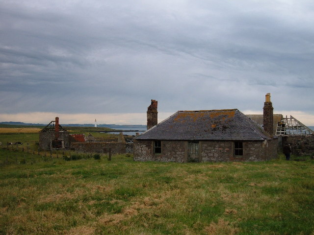 Abandoned cottages.  Scurdy Ness lighthouse behind.