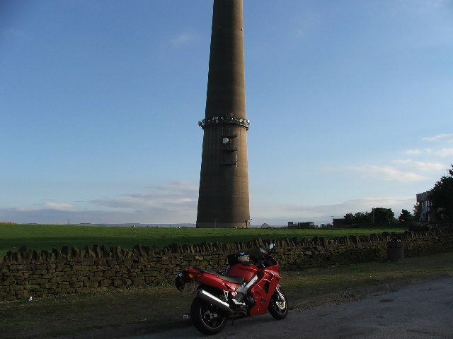 Bike, bin and wall at roadside near, but not in the same square as Emley Moor Mast