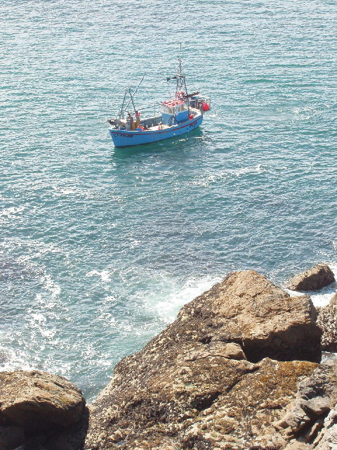 Rocks at the base of Park Head, with fishing boat
