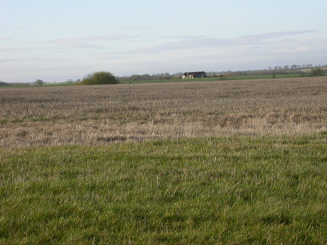 Field of stubble and farm building