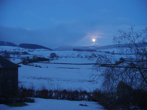 Full moon rising over snowfields.