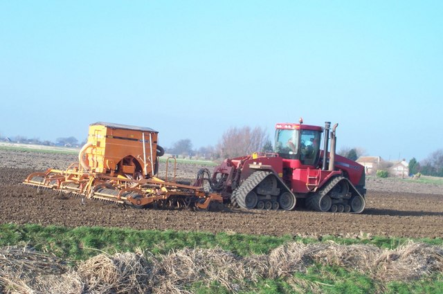 Large articulated tractor sowing wheat