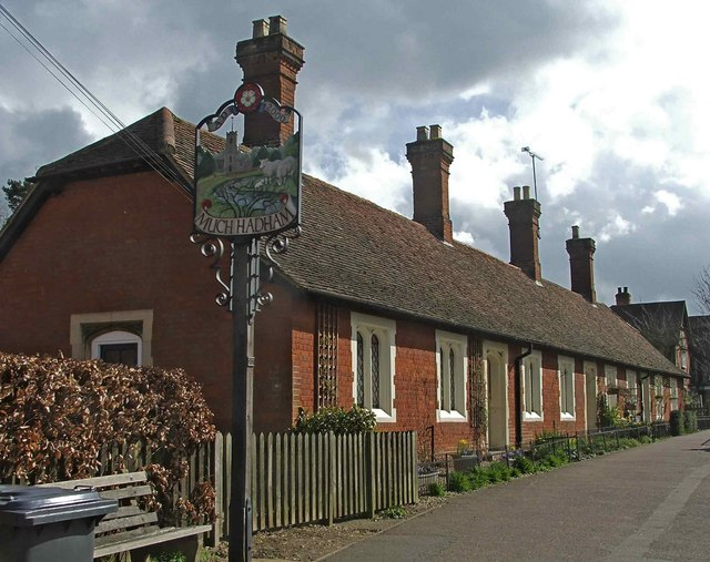 Almshouses, High Street, Much Hadham, with village sign.