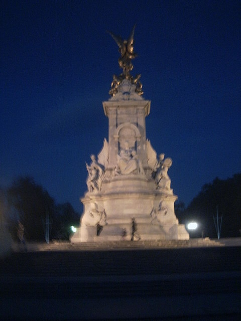 Monument outside Buck House at night.